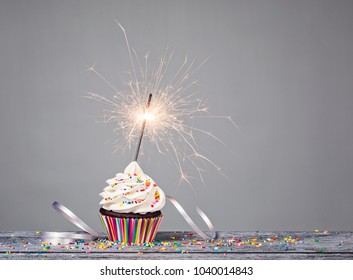 Cupcake with sprinkles and a sparkler over a gray background.
