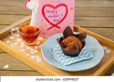 Cupcake, tea, flower vase and happy mothers day greetings card in tray on wooden plank