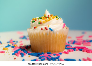 Cupcake with white cream and sugar icing on blue background macro shallow depth of field view. Homemade vanilla cup cake with buttercream icing and frosting close up. Holiday and birthday.
