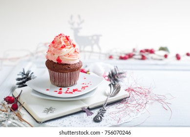 Cupcake with white and red cream over Christmas background