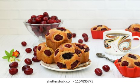 Cupcakes with berries are located on a plate on a white background. In the photo there are cupcakes in molds, a cup of coffee and a vase with berries.