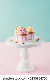 cupcakes with buttercream and candies on cake stand
