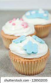 cupcakes with butter-cream and flowers and hearts on a textile tablecloth background