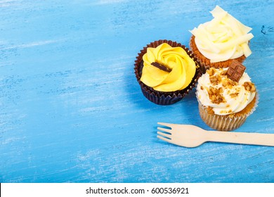 Cupcakes with buttercream. Sweet cake with cream and small chocolate bar. Dessert with topping and fork. On blue wooden rustic background.