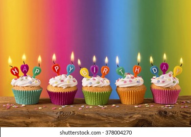 Cupcakes with candles on colorful background