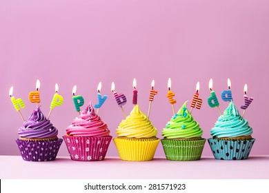 """Cupcakes with candles spelling the words """"happy birthday"""""""
