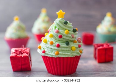 Cupcakes with christmas tree shape and christmas decoration on wood