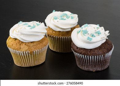 Cupcakes with cream on the wood background