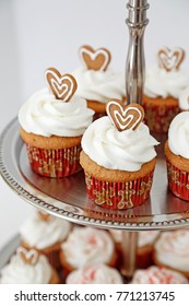 Cupcakes decorated with gingerbread hearts in a two tier stand.