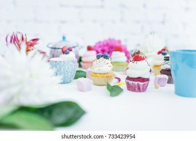 Cupcakes with fresh berries flowers and leaves, a cup of tea or coffee.
