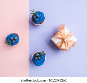 Cupcakes and gift box over two color plain background. Top view.