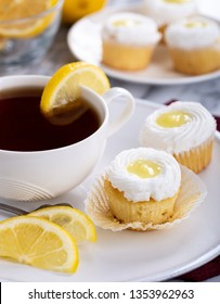 Cupcakes with lemon filling and white icing and a cup of tea on a plate