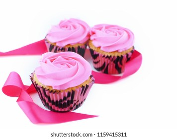 Cupcakes with pink icing and pink ribbon for Breast Cancer Awareness month in October. Copy space