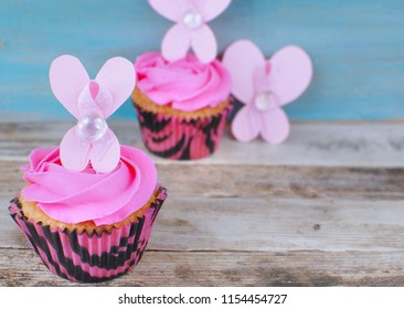 Cupcakes with pink icing and pink ribbon on a cut out paper butterfly decoration for Breast Cancer Awareness month in October. Wooden table and blue background