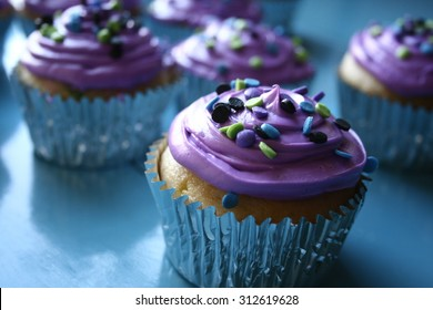 Cupcakes with purple frosting and sprinkles