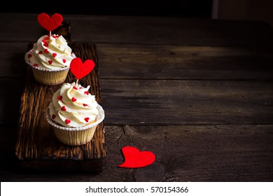 Cupcakes with red hearts for St. Valentines Day. Selective focus, Dark wooden background. Style rustic, place for text.