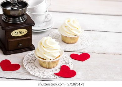 Cupcakes with red hearts for St. Valentines Day.White wooden background.Place for text. Selective focus