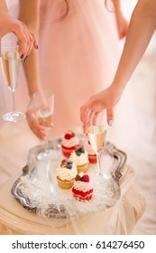 cupcakes red velvet with strawberries raspberries blueberries with cream chocolate on a tray, three girls delicate pink dress take the glasses of champagne from the table