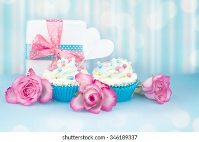 Cupcakes with roses and gift box.