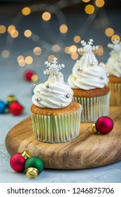 Cupcakes with vanilla cream, snowflakes and colorful Christmas balls on a wooden serving board on a blurred background of lights, selective focus.