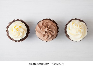 Cupcakes with whipped chocolate and vanila cream, on white wooden table. Picture for a menu or a confectionery catalog. Top view.