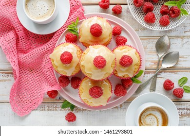 Cupcakes with white chocolate and fresh raspberries on a ceramic plate on a wooden white table, top view. A delicious dessert or breakfast.