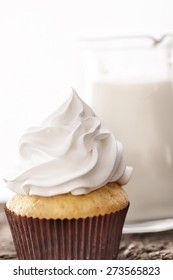 Cupcakes with white cream on background of a carafe of milk on wooden table