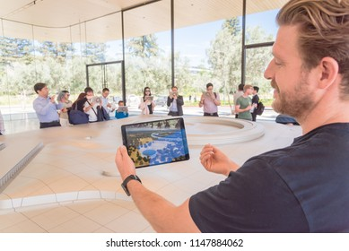 CUPERTINO, CA, US-JUL 18, 2018:Happy employee showing iPad with augmented reality technology and three-dimensional model of the Apple Park campus. Exhibition to illustrate new Apple office building
