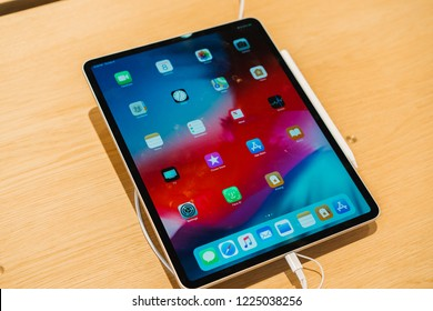 Cupertino, California / USA - November, 8, 2018 Apple Store New Product, - Silver Ipad Pro with 12.9 inch Liquid retina display connected to usb C charger on wooden table.  Modern design tablet model