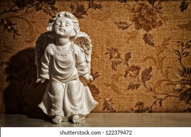 cupid sculpture with floral background vintage
