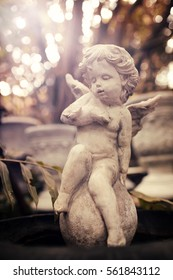 Cupid sculpture in garden, background for Valentine's day. color toned.