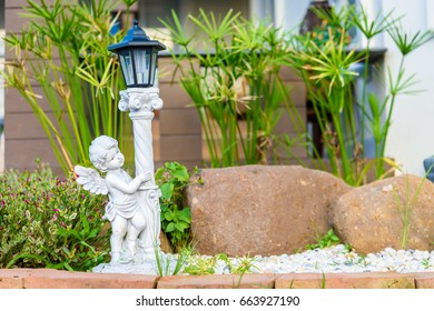 cupid sculpture with lamp in small garden