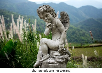 cupid statue among meadow morning