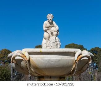 Cupid statue in the fountain of the Garden of Roses in Buen Retiro Park. Parque De Las Rosas in Spanish) in Botanical Garden in Park of Retiro. Madrid, Spain.