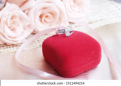 A cuple of diamond rings , wedding rings, are on the red box and pale peach roses for background. The moment of wedding day, anniversary, engagement or valentine's day. Happy sweetest day.