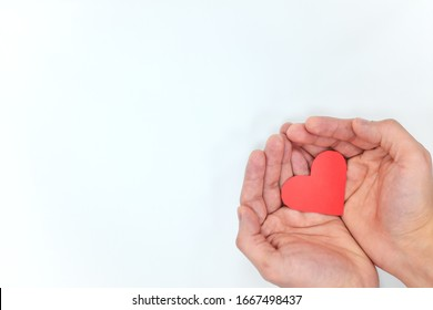 Cupped hands holding a red heart in white background top view. Love, kindness and give hope concept.