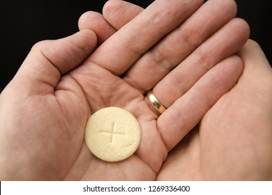 Cupped hands of a man holding a wafer of bread The Body of Christ when receiving communion at a Roman Catholic Mass