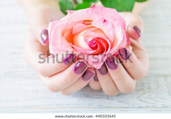 Cupped hands with manicured fingernails holding delicate roses