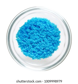 Cupric sulfate in glass bowl, isolated on white background. Bright blue copper sulfate CuSO4, also blue vitriol or bluestone. Salt, used in swimming pools, fireworks and in schools to grow crystals.