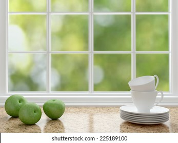 Cups and apples on the marble worktop in front of big window. White kitchen design.