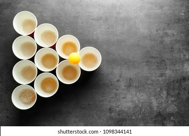 Cups and ball for beer pong on table, top view