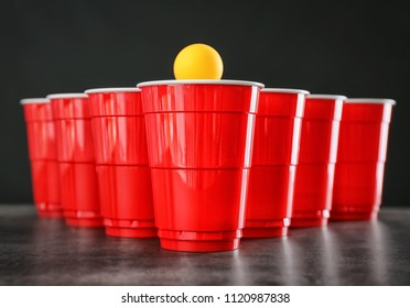 Cups and ball for beer pong on table