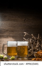 Cups beer, hops, pretzels, wheat spikelets on empty wooden background