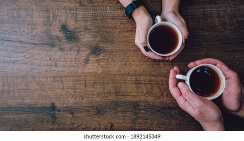 Cups of black tea or coffee in the hands of men and women. on a wooden background. with copy space. top view
