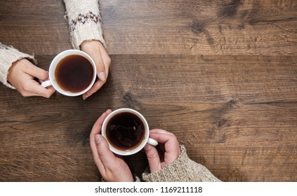 Cups of black tea in the hands of men and women. on a wooden background. with copy space. top view