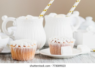 Cups with cacao and marshmallow, cupcakes and different decorations, soft focus background
