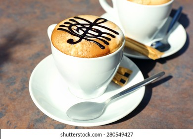 Cups of cappuccino with treble clef on foam on table in cafe