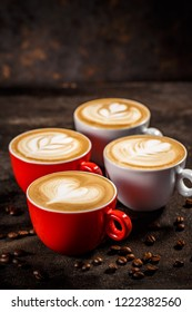 Cups of cappuccino with trendy shapes latte art