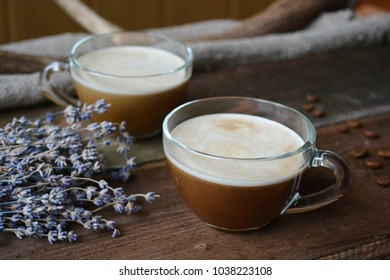 Cups of coffee with cream on wooden background