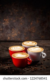 Cups of coffee on dark background. Latte art in different shapes